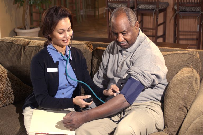A visiting nurse checks a patient's blood pressure.