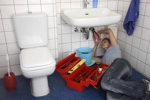 woman working on bathroom sink with tools