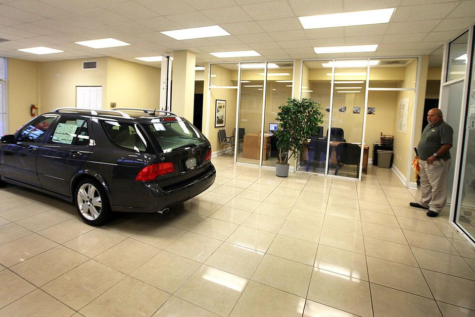 Sales Consultant, Mike Selcis, looks at the Saab wagon on the showroom floor at the Deel Saab dealership on December 18, 2009 in Miami, Florida.