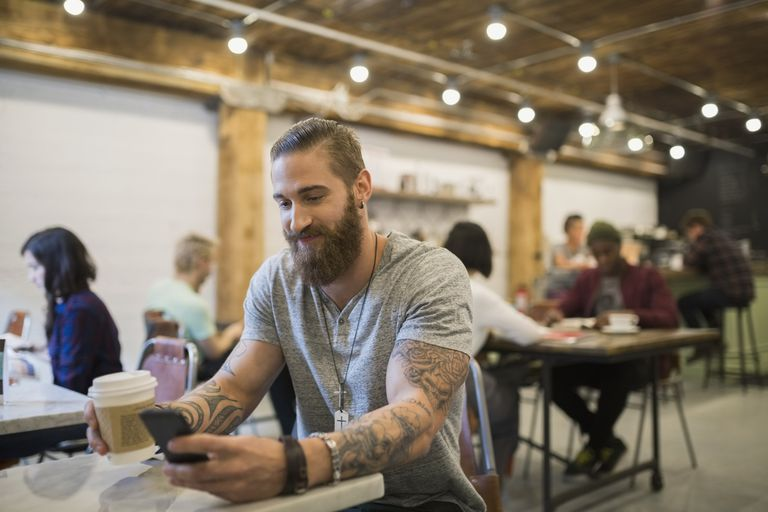man using smartphone in busy coffee shop