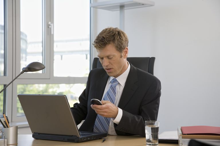 Businessman using cell phone and laptop at desk