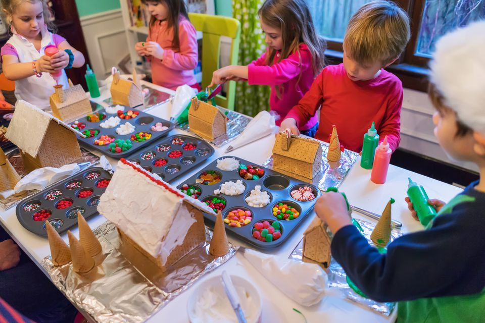 Group of children decorating gingerbread houses at Christmas