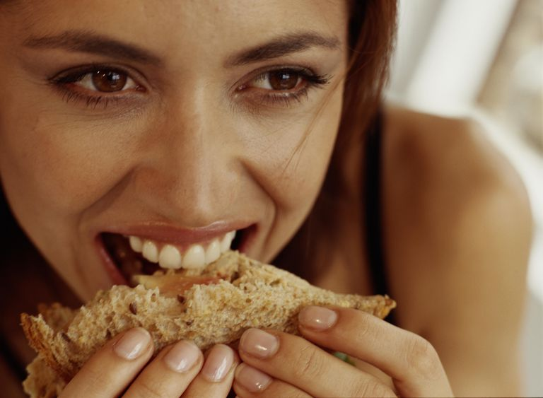 Young woman eating sandwich, close-up