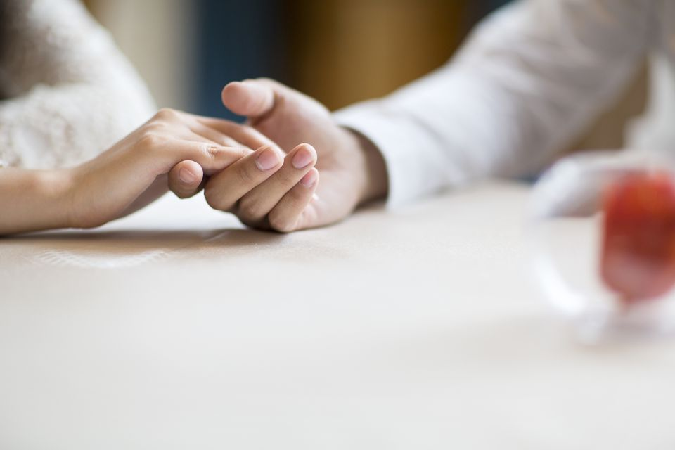 couple holding hands at dinner table