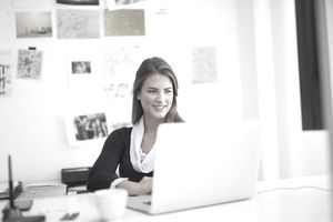 Smiling young woman using a laptop at her desk to answer questions to provide feedback for a coworker's 360 nfeedback process.