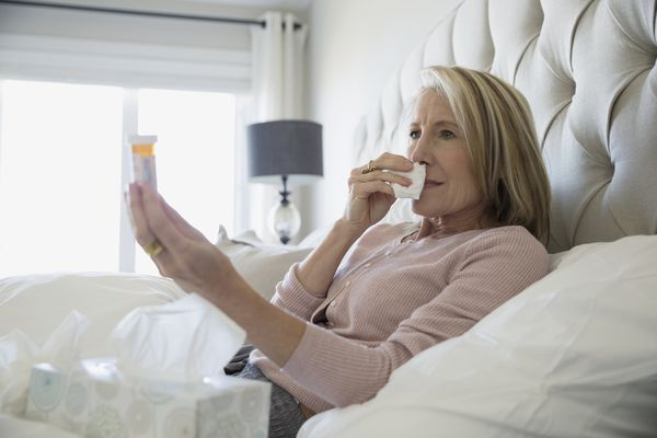 Sick woman in bed holding pill bottle.