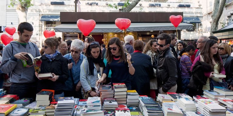men and women looking at book stacked at booth with heart balloons in background at St. Jordi / Day of the Book festival Barcelona