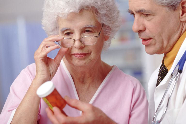 Woman and doctor reviewing pill bottle directions.