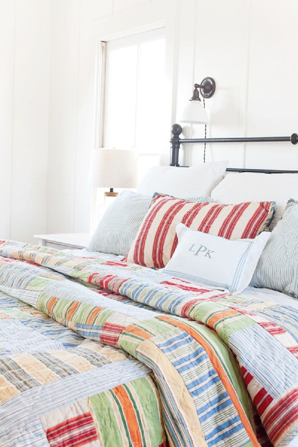Colorful quilt in farmhouse bedroom