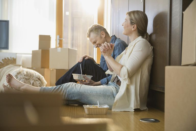 Couple eating take out food near moving boxes