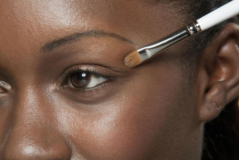 a woman putting on eye shadow