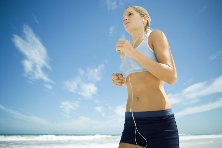Young woman jogging on beach, listening to MP3 player, low angle view
