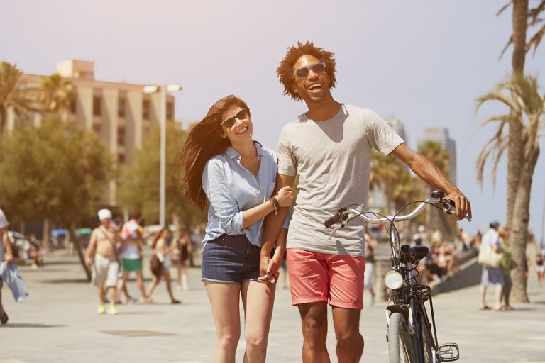 Couple with bicycle walking on street