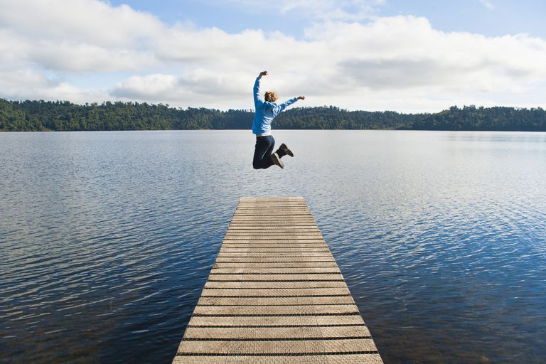 Woman jumping on dock in the water