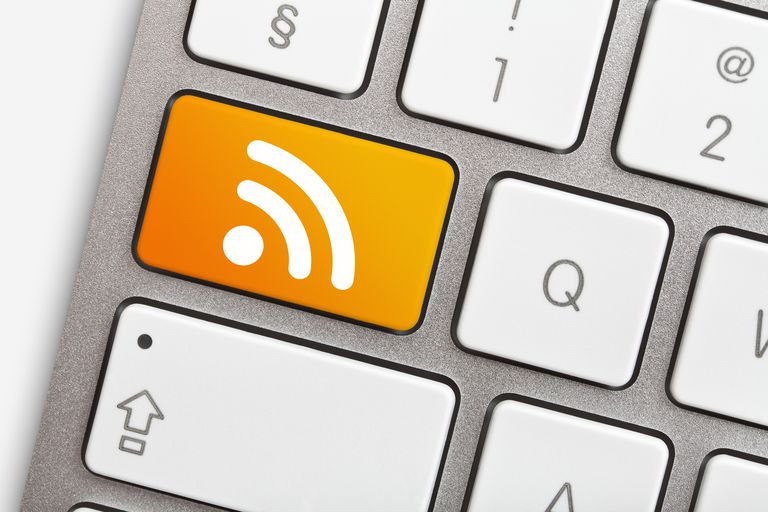 RSS feed symbol, white network sign on orange background, shown on a keyboard