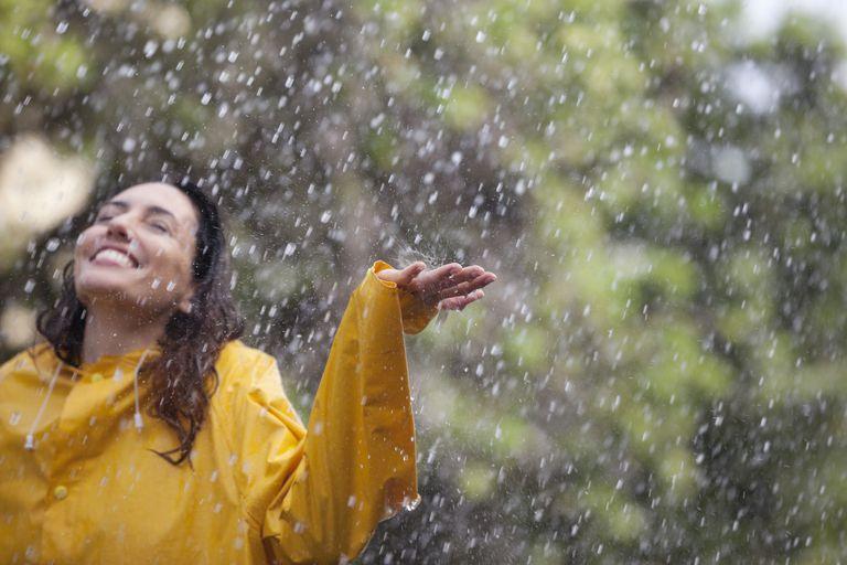 Mujer sonriendo bajo la lluvia