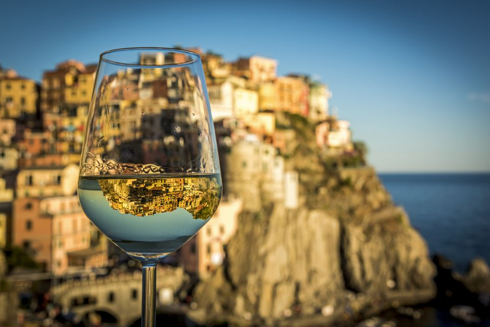 Italy, Cinque Terre, Manarola, View of village with reflection in wine glass