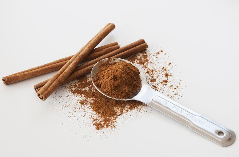 cinnamon stick and cinnamon powder in a teaspoon