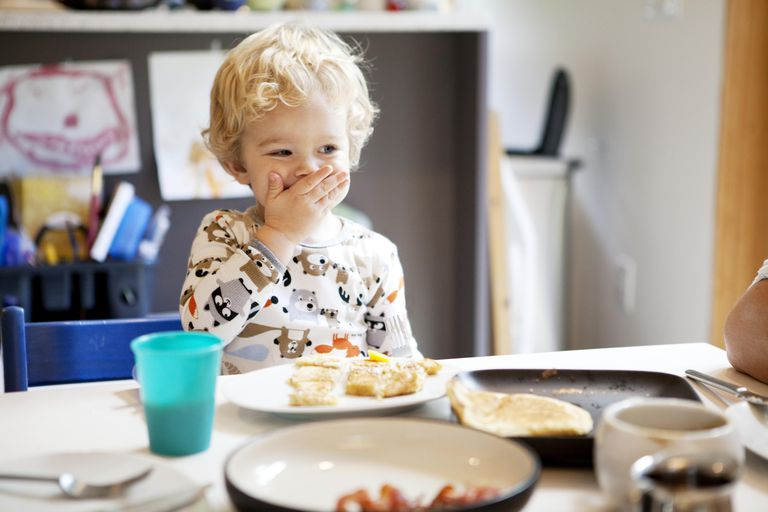 Toddler eating breakfast with his hands, smiling