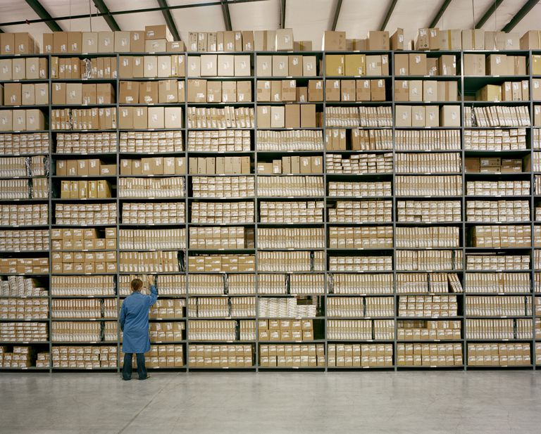 Female worker pulls box off of warehouse shelf