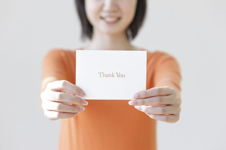 Woman holding out a thank you note