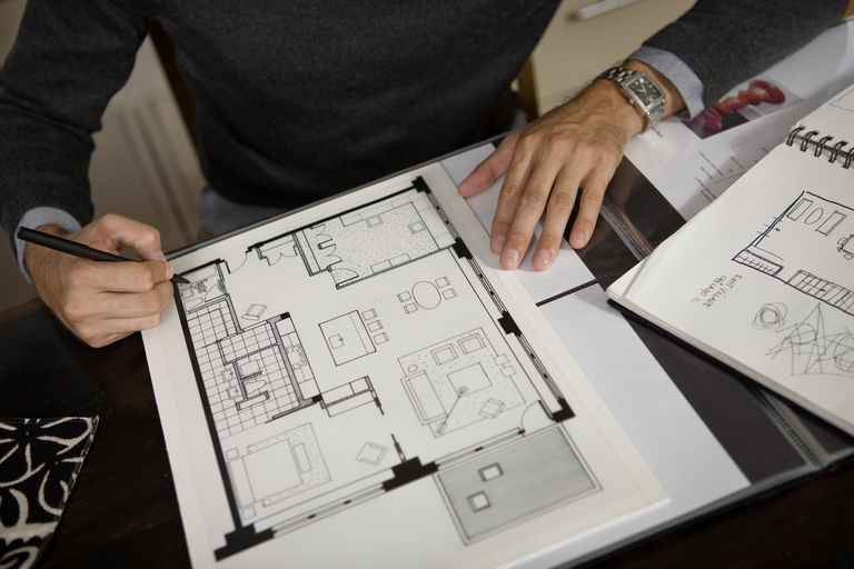 A person adjusting floor plans in spiral bound sketch notebooks
