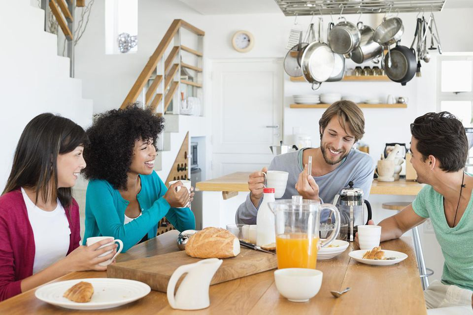 Friends sitting at a dining table having breakfast