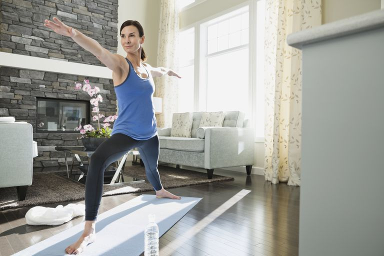 Mature woman practicing yoga in living room
