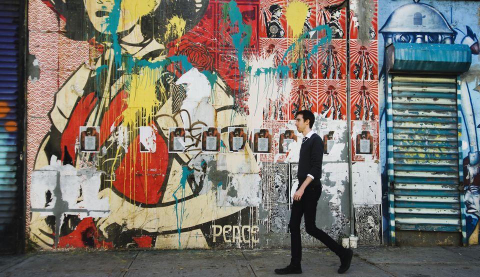 Man walking past a graffiti wall in Williamsburg, Brooklyn