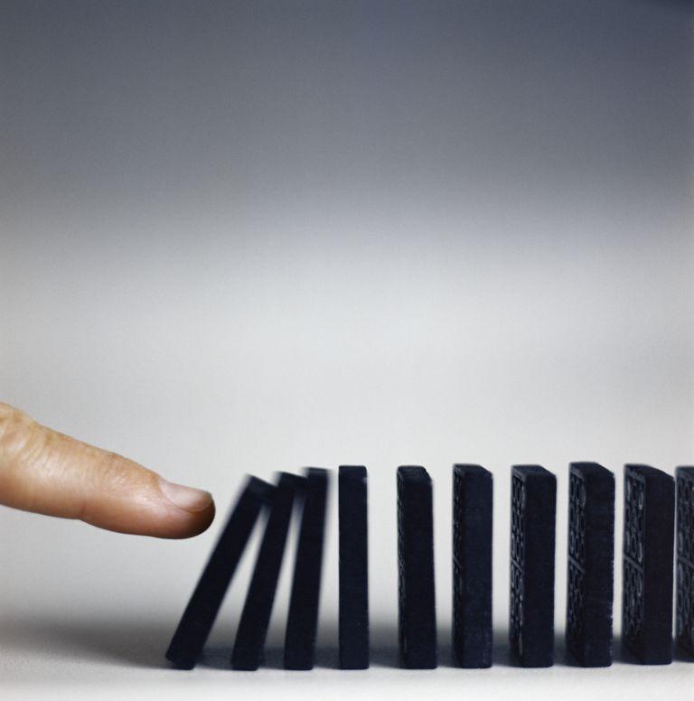 Dedo empujando fila de dominos