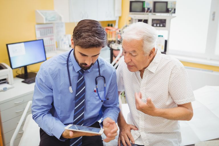 Doctor discussing with patient over digital tablet