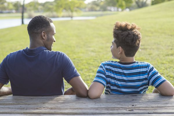 Father and son sitting at table in park