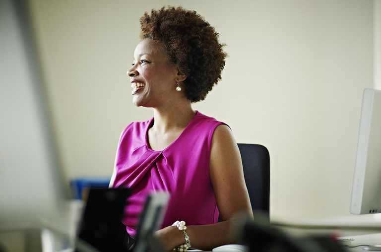 Businesswoman in discussion at workstation smiling