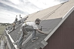A team of workers installing a new roof on a building.