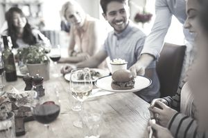 Waiter serving slider hamburger to woman dining with friends at restaurant table