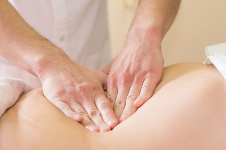 A massage therapist's hands press on a client's back.