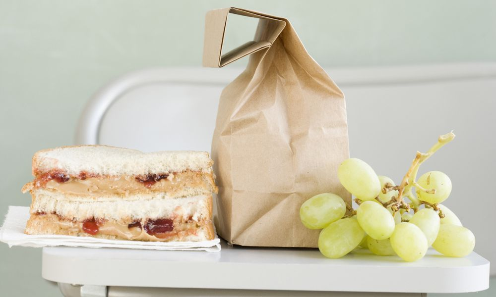 Peanut butter sandwich with a brown paper bag and bunch of grapes