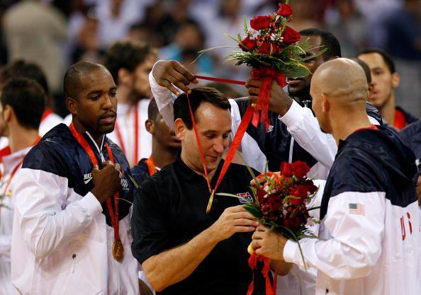 LeBron James hangs his Olympic gold medal around the neck of Team USA coach Mike Krzyzewski