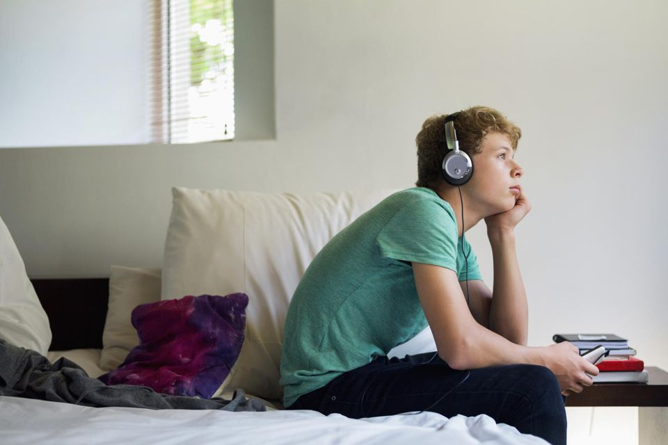 Teenage boy listening to music on a mobile phone.