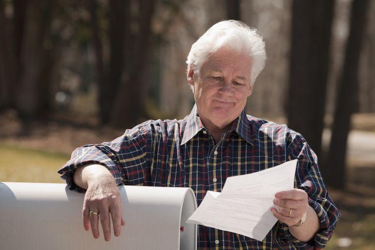 USA, Virginia, Richmond, senior man reading letter by mailbox