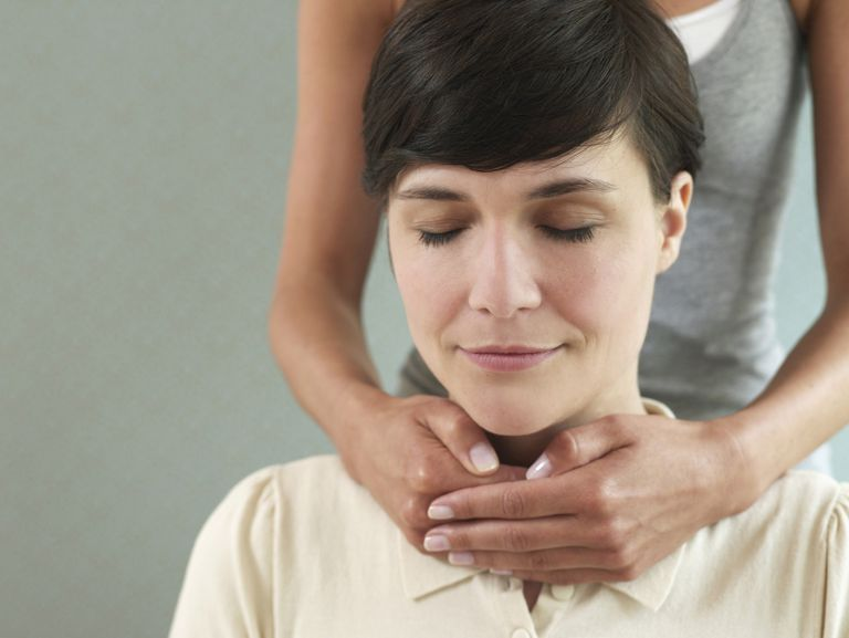 Reiki being given to a woman sitting in a chair