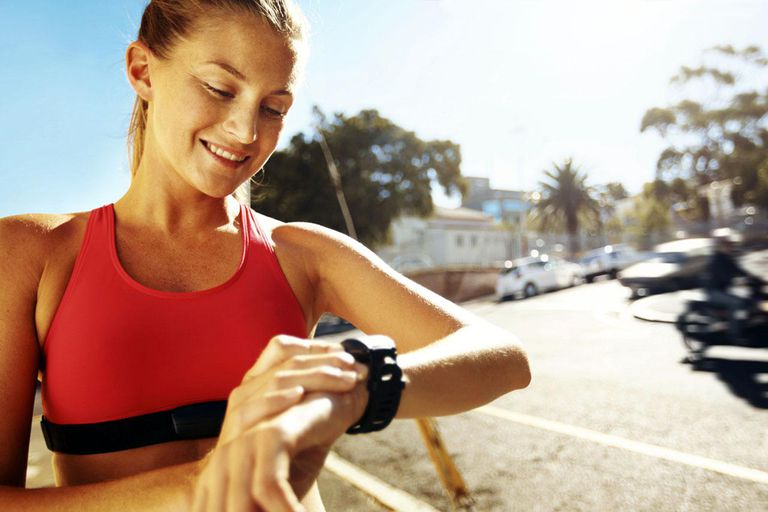A pretty young runner looking at her stopwatch after a run along the road