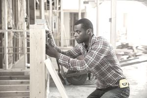 Construction worker measuring structure on site