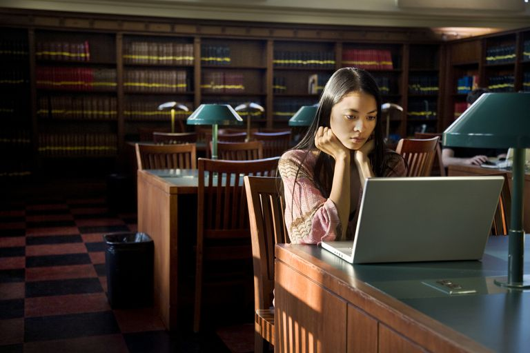Young Woman Using Laptop in Library