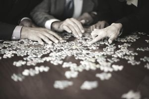 Business professionals collaborating on a jigsaw puzzle