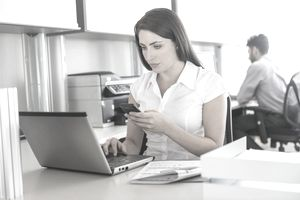 Woman working on laptop and text messaging in office, man in background