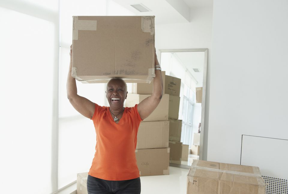 African American woman holding a packed moving box above her head