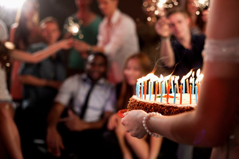 Person carrying birthday cake, group of friends in background