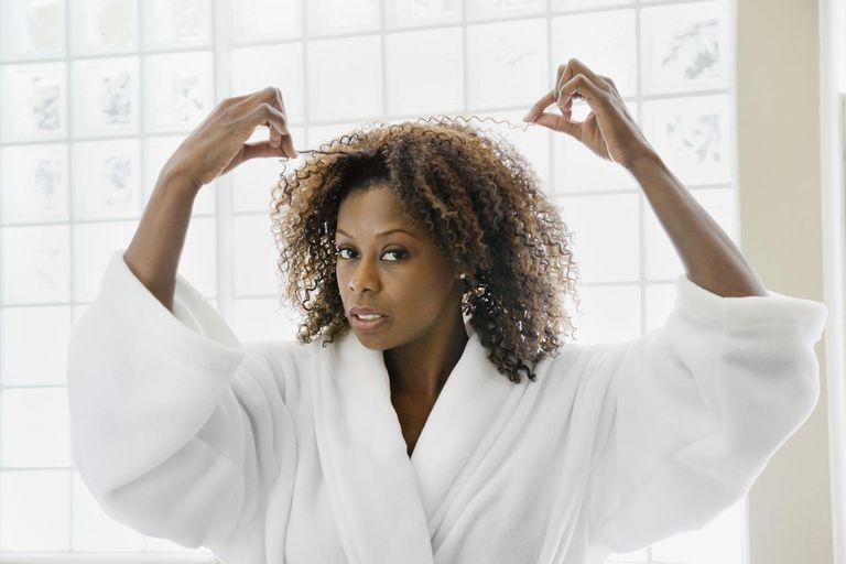 African woman pulling frizzy hair in bathroom