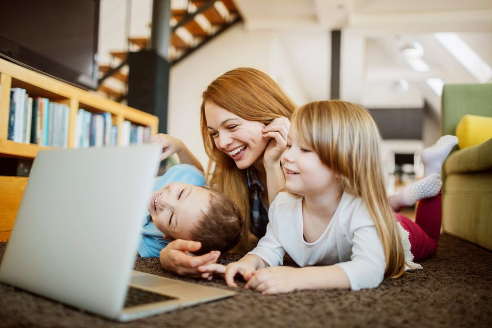 A picture of a mom with her kids looking at a computer